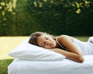Teenage girl sleeping on soft mattress and pillow on grass outsi