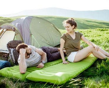 Young And Cheerful Couple Lying On The Mattress At The Campsite,